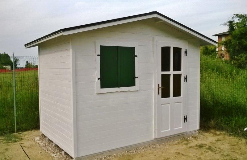 Casetta in legno bianca con finestra verde foresta