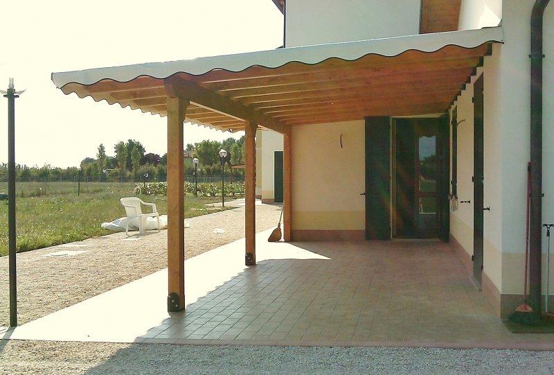Tettoia in legno addossata con areele e telo in PVC