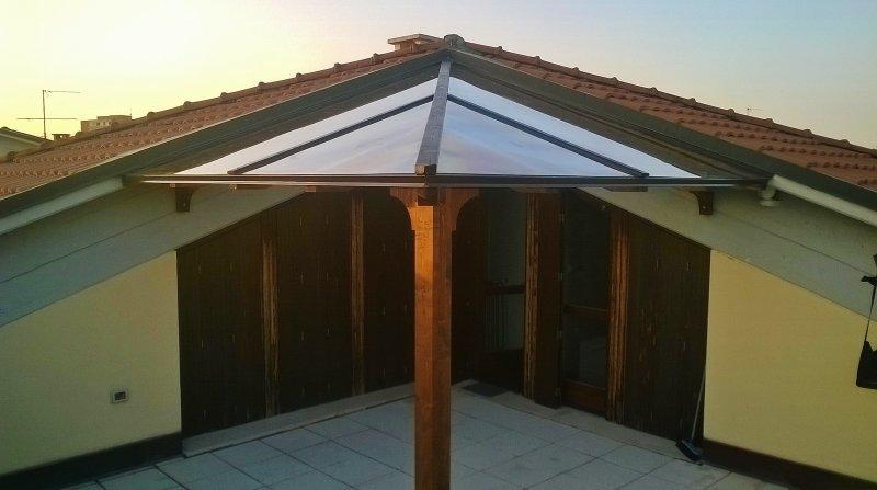 Tettoia a due falde in legno con copertura in policarbonato compatto