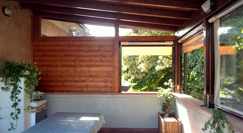 tettoia su terrazzo con chiusure parziali in legno e tende