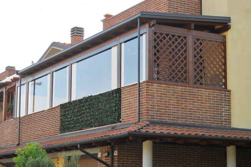 Tettoia in legno su terrazzo con tende frontali avvolgibili